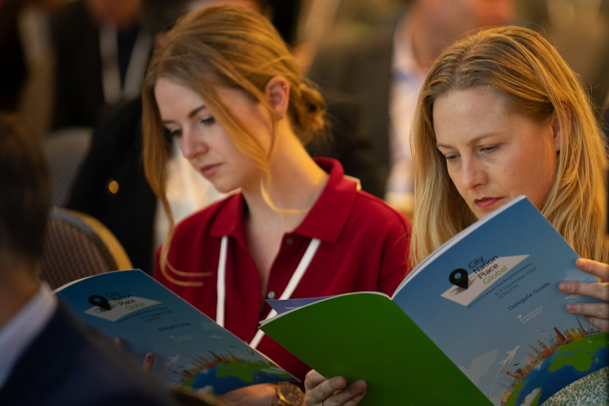 Two people reading delegate books
