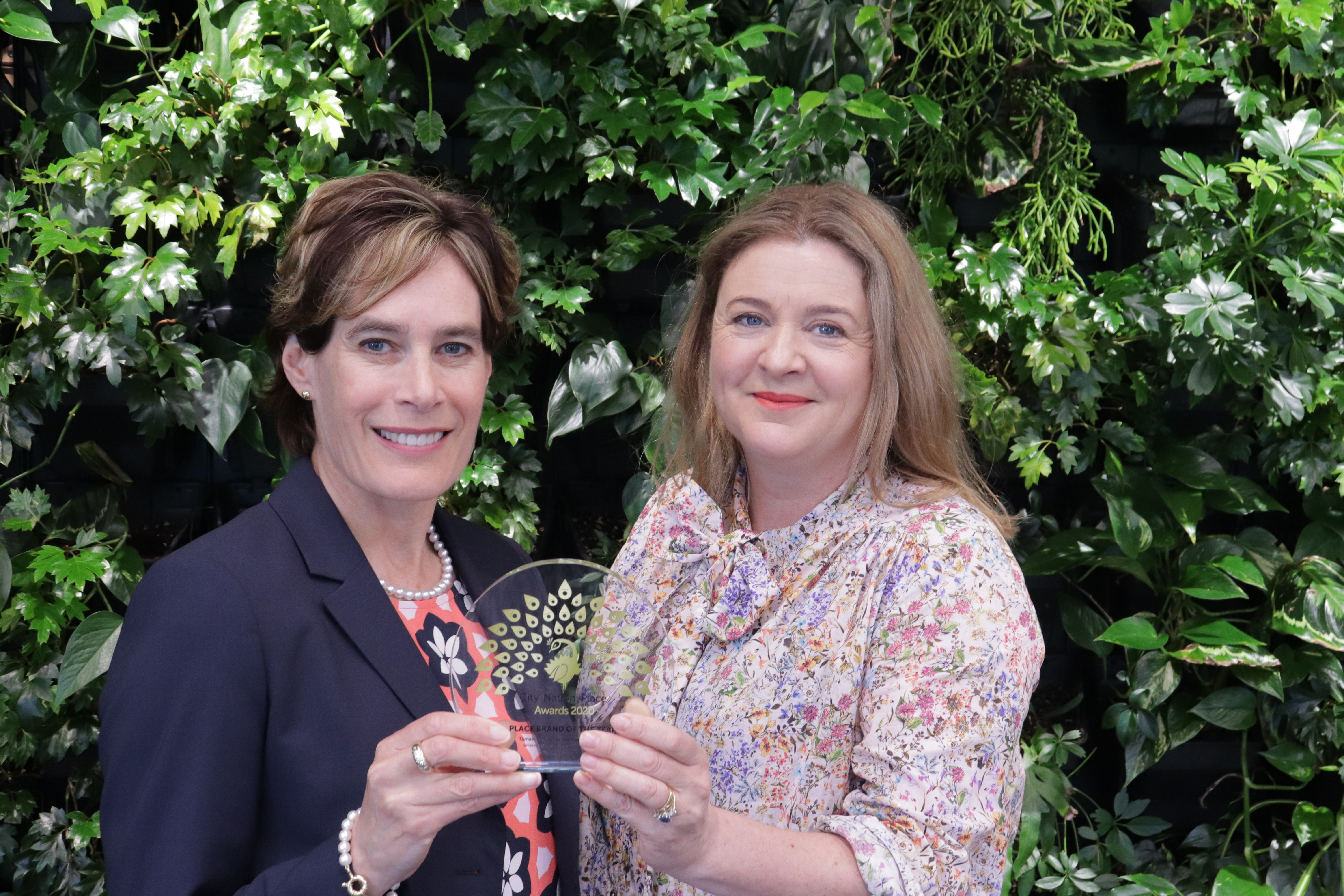 Two team members from Auckland Tourism, Event, and Economic Development, celebrate with their award for Place Brand of the Year
