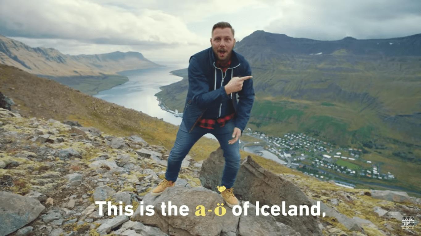 "Picture of man on a mountain singing ""The A to Ö of Iceland."""