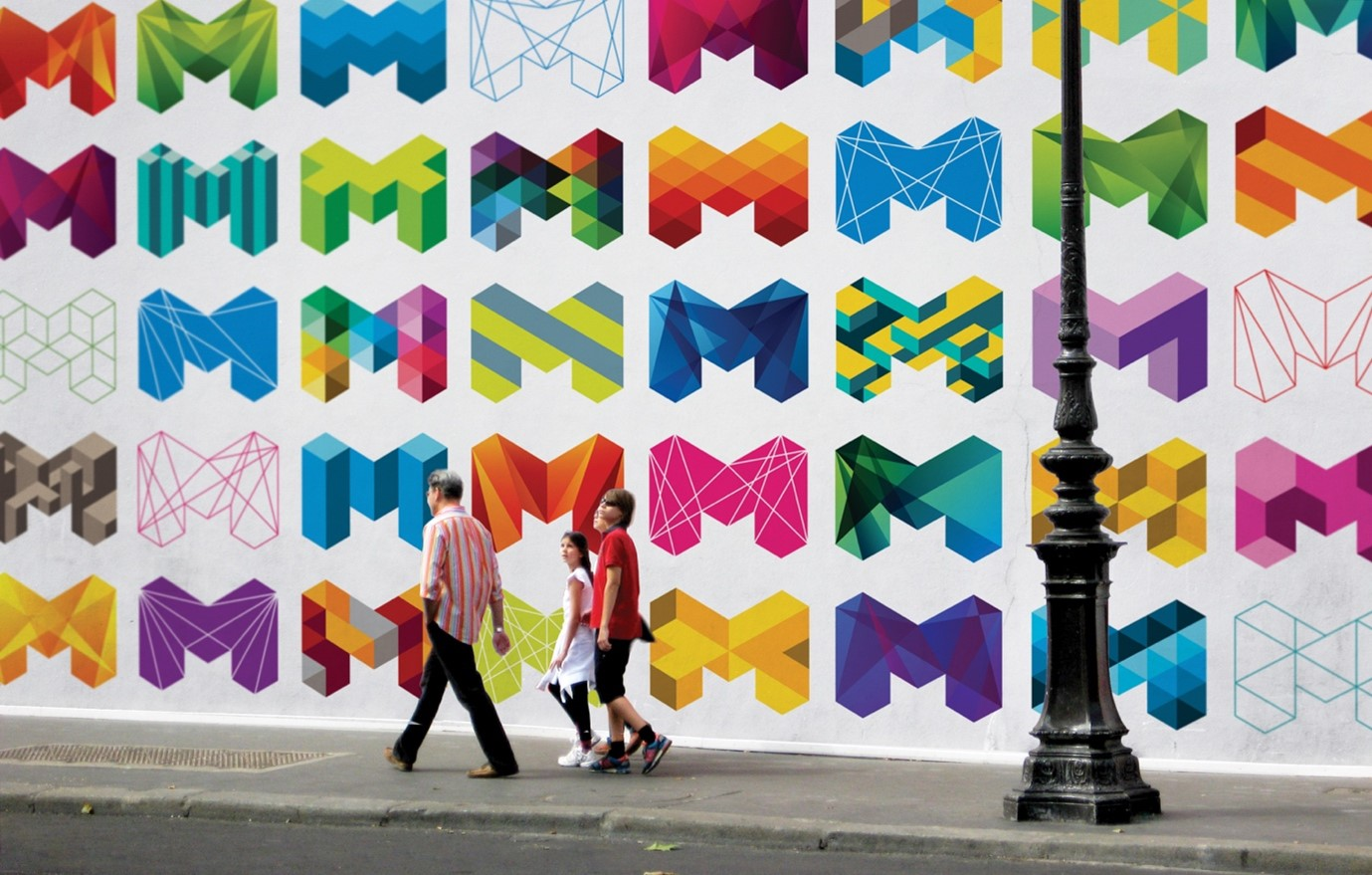 Three people walking past an example of Melbourne's branding.