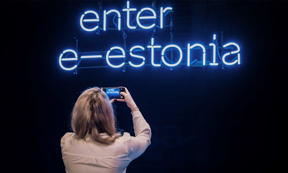 Woman photographing a neon Enter E-Estonia sign